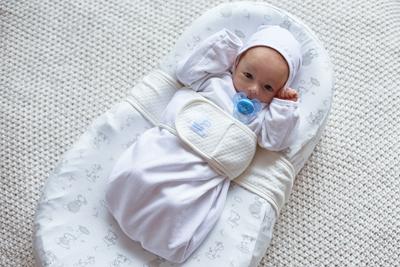 Ребенок лежит в коконе для новорожденных фото